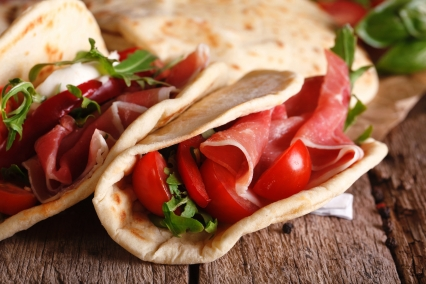 Italian piadina flatbread stuffed with ham and vegetables close-up on the table. horizontal